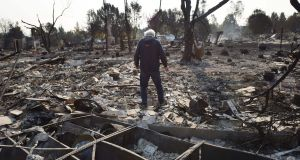 Santa Rosa resident Phil Rush looks at the remains of his home destroyed by wildfire. Photograph:  Robyn Beck/AFP/Getty Images
