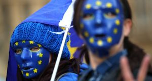 People dressed in EU flag colours  demonstrating outside the Houses of Parliament, in central London. Photograph: Hannah McKay/Reuters