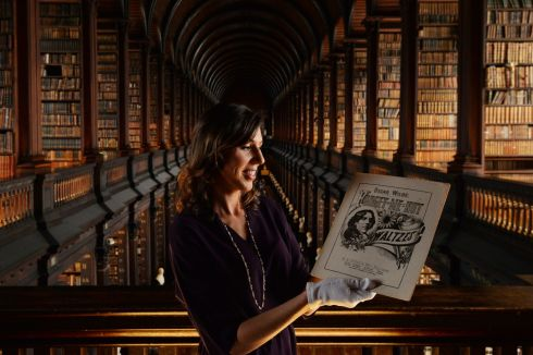 WILDE WALTZES: Curator Caoimhe Ní Ghormáin with sheet music of dances inspired by Oscar Wilde, part of From Decadence to Despair, the first big Irish exhibition about the writer, in the Long Room of the Old Library at Trinity College Dublin. Photograph: Alan Betson