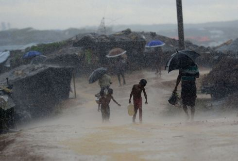 ROHINGYA STRUGGLE: A child carrries water through a drenched refugee camp at Kutupalong, in Bangladesh. Nearly a million Rohingya are now crowded into packed camps near the border with Myanmar; most live in desperate conditions with limited access to food, clean water or proper sanitation. Photograph: Munir Uz Zaman/AFP/Getty