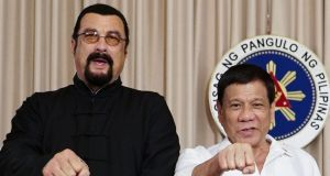 Philippines president Rodrigo Duterte gives his signature fist bump with US actor Steven Seagal, in Manila. Photograph: PPD/AFP/Getty Images