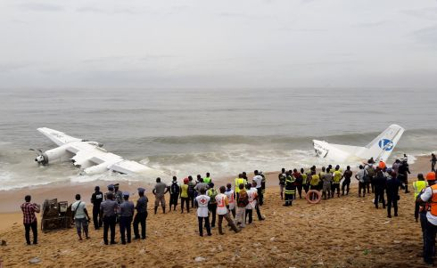 PLANE CRASH: Policemen and rescuers stand near the wreckage of a cargo plane after it crashed in the sea near the international airport in Abidjan, the Ivory Coast. Photograph: Luc Gnago/Reuters