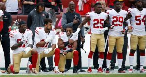 Eli Harold, Arik Armstead and K'Waun Williams of the San Francisco 49ers kneel during the national anthem before their game against the Washington Redskins at FedEx Field in Landover, Maryland. Photo: Joe Robbins/Getty Images