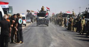 Members of Iraqi federal forces  advance in military vehicles in Kirkuk, Iraq on Monday. Photograph: Reuters