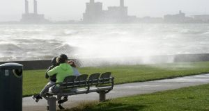People watch waves splash over the wall on Coast Road Clontarf, ahead of Hurricane Ophelia hitting Dublin. Photograph: Dara Mac Dónaill/The Irish Times