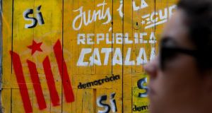 A woman walks past a pro-independence graffiti in a street in Barcelona on Monday. Photograph:  Gonzalo Fuentes/Reuters