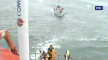 RNLI lifeboat rescue ten-metre yacht with three people on board