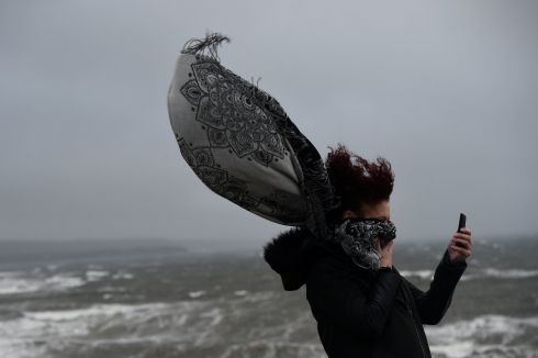 A woman takes a picture during storm Ophelia in the County Clare town of Lahinch, Ireland October 16, 2017. REUTERS/Clodagh Kilcoyne