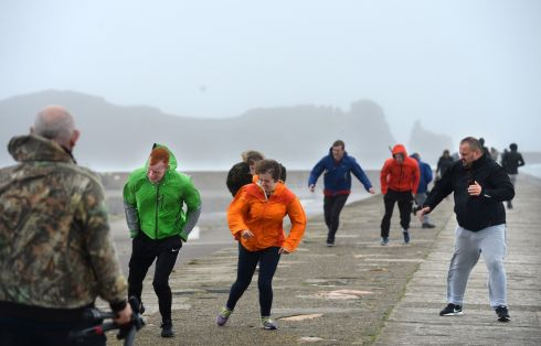 People walk the pier at Howth while Hurricane Ophelia hit Dublin.  Photograph: Dara Mac Donaill / The Irish Times
