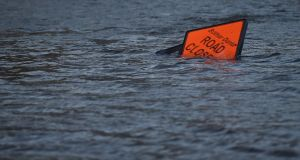 A 'road closed' sign is seen submerged in floodwater during Storm Ophelia in Galway. Photograph:  Clodagh Kilcoyne/Reuters