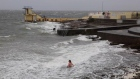 Bather swims in Atlantic ocean during Storm Ophelia