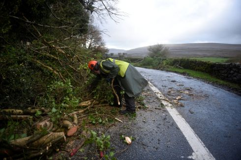 A worker clears fallen trees off a road during Storm Ophelia in the Burren.  Photograph: Clodagh Kilcoyne /Reuters