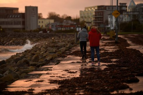 People walk on a seaweed-covered path after Storm Ophelia passed through Galway.  Photograph: Clodagh Kilcoyne / Reuters