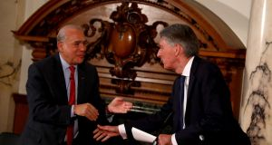 OECD secretary-general Angel Gurria shakes hands with  Britain's chancellor of the exchequer Phillip Hammond: any threat to the peace process in Northern Ireland from the introduction of a hard Border would damage UK economic growth. Photograph: Neil  Hall/EPA