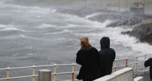 People watch the waves and sea spray in Lahinch, Co Clare. Photograph: Niall Carson/PA