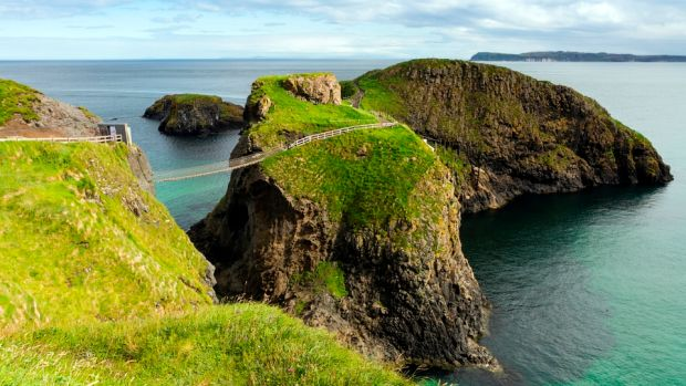 Carrick-a-Rede rope bridge with neighbouring Rathlin Island on the horizon