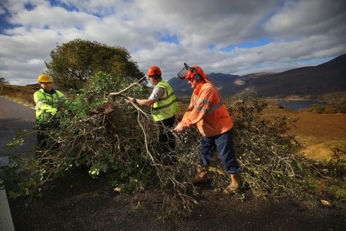 KERRY CLEAN-UP: Tree surgeon Ger Brosnan (centre), with staff from Kerry County Council, Donal O'Connell (left) and John Lehane, clearing and cutting trees along the Moll's Gap Road between Killarney and Kenmare, which was closed on Tuesday after Storm Ophelia. Photograph: Valerie O'Sullivan