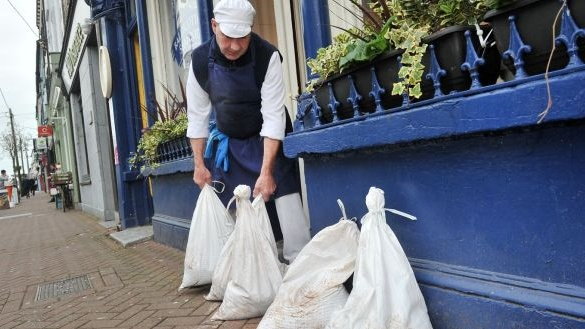 Fishmonger Colm O'Riordan of Ballycotton Seafood, Midleton, east Cork places sandbags by his shop door. Photograph: Daragh Mc Sweeney/Provision