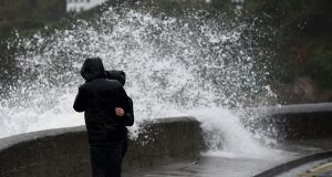 A wave breaks over a wall as bystanders look out across the Irish Sea during Storm Brian in Dublin, Ireland on Saturday. Photograph: Clodagh Kilcoyne/Reuters