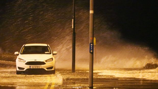 A parked car is seen at Salthill in Galway as waves crash over the promenade. Photograph: PA