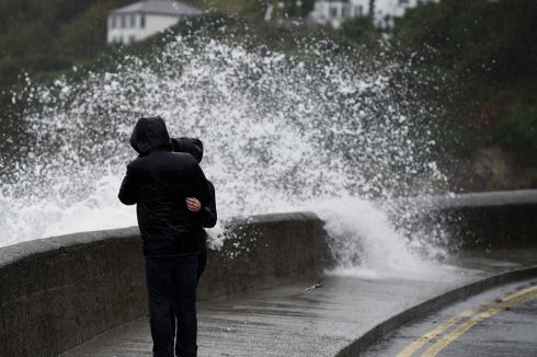 A wave breaks over a wall as bystanders look out across the Irish Sea. Photograph: REUTERS/Clodagh Kilcoyne