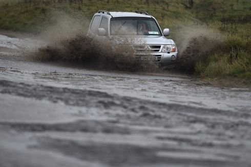 DRIVING RAIN: A driver steers through flood water caused by Storm Brian, along Bull Wall in Dublin. Photograph: Clodagh Kilcoyne/Reuters