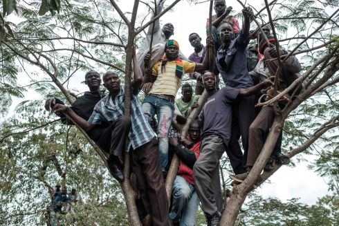 STANDING ROOM ONLY: Supporters of Kenya's opposition National Super Alliance coalition climb a tree to watch the funeral service for the three victims who were allegedly shot by police as they attended a demonstration last week in Bondo. Photograph: Yasuyoshi Chiba/AFP/Getty Images