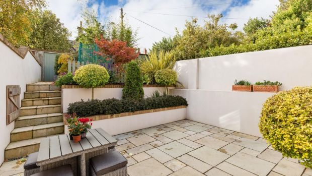 The doors open out to a valuable south-facing flagstone patio and a garden landscaped by Garden Transformation that is stepped to the back, rising to meet the southern aspect sunlight.