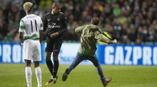 A pitch invader tries to kick Kylian Mbappe during Celtic's 6-0 defeat to PSG. Photograph: Steve Walsh/Getty