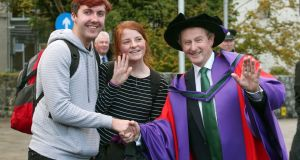 Enda Kenny  with first-year students Seán Reynolds and Ellen Healy at NUI Galway where he received an honorary doctorate in laws. Photograph: Joe O'Shaughnessy