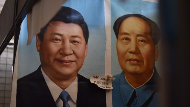 Painted portraits of Chinese President Xi Jinping (left) and late communist leader Mao Zedong at a market in Beijing. Photograph: Greg Baker/AFP/Getty Images