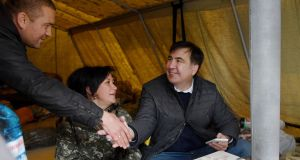 A man shakes hands with former Georgian president Mikheil Saakashvili as he sits in a tent during a protest against Ukrainian president Petro Poroshenko in Kiev on Sunday. Photograph: Sergei Supinsky/AFP/Getty Images