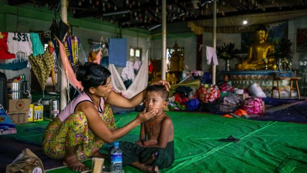A Buddhist woman and her son were staying at the Damarama Monastery, in Sittwe, after being displaced by violence in northern Rakhine. Photograph: Adam Dean/The New York Times