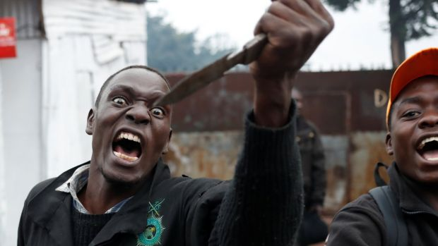 An opposition supporter gestures with a knife during clashes with police in Kibera slum in Nairobi on Thursday. Photograph: Goran Tomasevic/Reuters