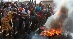 People gesture near tyres set on fire during a protest against a presidential election re-run in  Mombasa. Photograph:  Joseph Okanga/Reuters