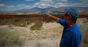 José Alfredo, who was deported from the US in 1999, points across the border from Mexico to where his mother and sister live in the US. Photograph: Stephen Starr