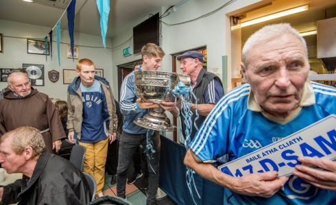 UP THE DUBS: Tom Mooney waits with his Sam-D-!7 sign as Sam Maguire was brought to the Capuchin Day Centre in Dublin where All-Ireland winners Michael Fitzsimons and Colm Basquel joined Br Kevin Crowley and guests to celebrate Dublin's three-in-a-row. Photograph: Brenda Fitzsimons/The Irish Times