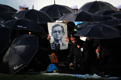 FALLEN HERO: Thai mourners hold black umbrellas and a picture of the late Thai King Bhumibol Adulyadej as they wait for the royal cremation ceremony outside the Royal Palace in Bangkok, Thailand. Photograph: Diego Azubel/EPA