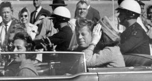 President John F Kennedy waves from his car  in Dallas, moments before he is shot. Photograph: AP Photo/Jim Altgens