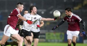 Omagh's Gregory Murray is challenged by  Slaughtneil's Meehaul McGrath. Photograph: Lorcan Doherty/Inpho