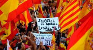 A protester holds a sign reading 'Being Catalan is a pride, being Spanish is an honour' as others wave Spanish and Catalan Senyera flags during a pro-unity demonstration in Barcelona. Photograph: Lluis Genelluis/AFP/Getty Images