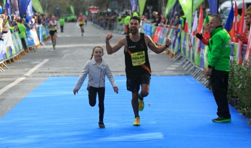 Abbie Nolan (9) helps her father  Karl Nolan, both from Clontarf, at the finish line during the SSE Airtricity Marathon in Dublin's city centre. Photograph: Gareth Chaney Collins