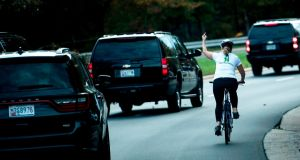 The cyclist gestured as the US president's motorcade passed. Photograph: Brendan Smialowski/AFP/Getty Images