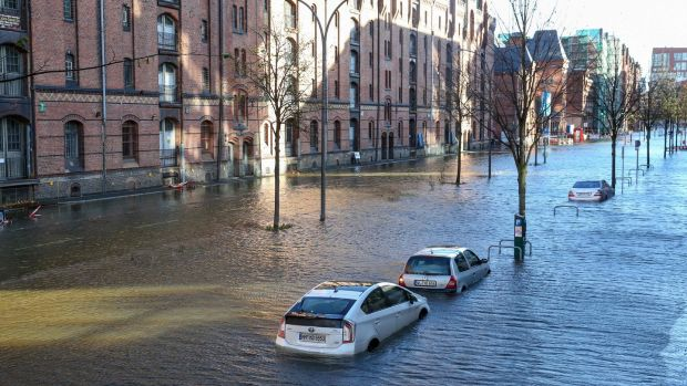 Flood waters surround cars parked at Hamburg's Fish Market district as a storm hit many parts of Germany. Photograph: Bodo Marks/Getty Images