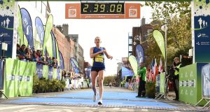 Laura Graham of Mourne Runners, Co Down, crosses the line at Merrion Square in Dublin city to be the first Irish finisher in the women's category of the Dublin Marathon. Photograph: Sam Barnes/Sportsfile