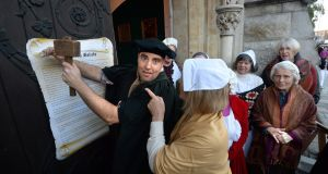 Patrick Rogers is challenged by Madeline Stringer and members of the Unitarian Church on the 500th anniversary of Martin Luther nailing his theses to the Wittenberg church door in 1517, re-enacted  on St Stephen's Green. Photograph: Cyril Byrne