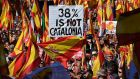 "Protesters wave Spanish and Catalan Senyera flag while holding a sign reading ""38 percent is not Catalonia""."