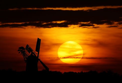 LAND OF THE SETTING SUN: The sun sets behind a windmill belonging to miller Nigel Moon in Whissendine, England. Photograph: Darren Staples/Reuters