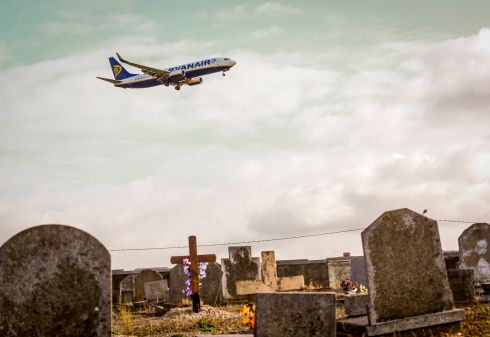 GOOD OMEN: A Ryanair plane flies near tombstones of the Ransart cemetery as it approaches Brussels South Charleroi Airport, in Belgium. A cemetery is only 60m away from the airport. Photograph: Olivier Hoslet/EPA