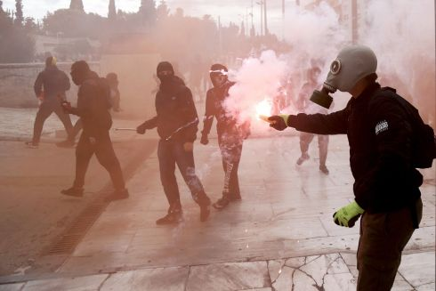 HAD ENOUGH: A masked protester throws a firework outside the Greek parliament during a students' protest against the education policy and the financial drain in education in central Athens. Photograph: Thanasis Kamvisis/EPA